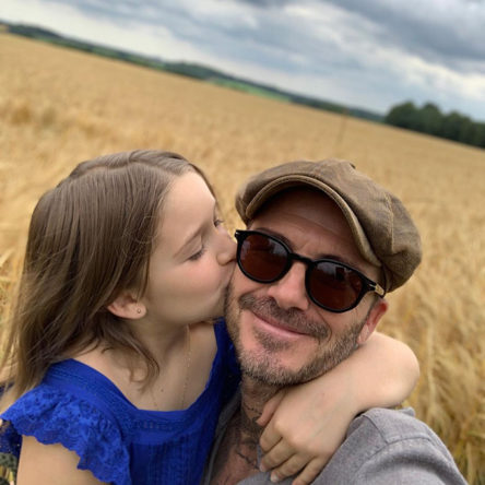 David Beckham being kissed on the cheek by his daughter, Harper Beckham