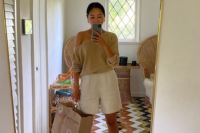 Aimee Song styles a pair of bermuda shorts with an off-the-shoulder sweater